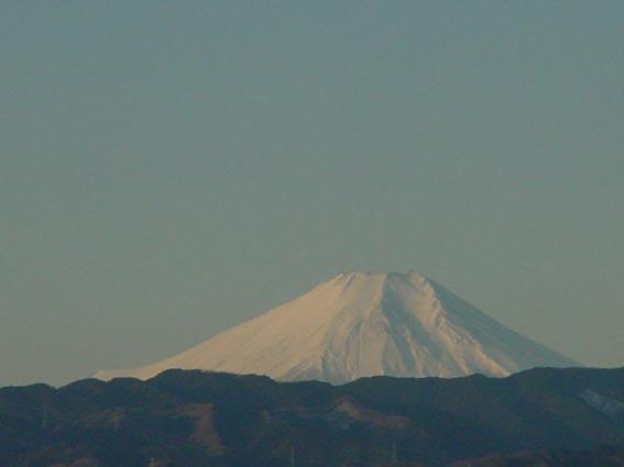 ④晴れた日の早朝、職場から南西方向の風景だそうです。米軍横田飛行場のむこうに見える朝焼けの富士山。